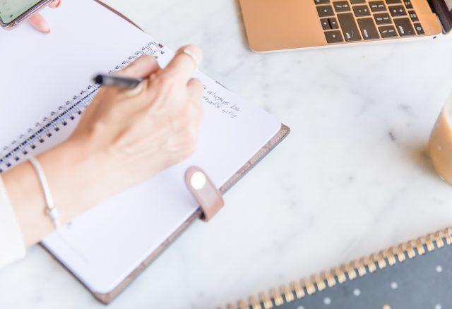 Freelance B2B copywriter writing in notebook