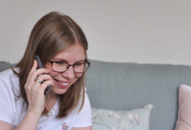 Freelance copywriter female smiling while talking on the phone