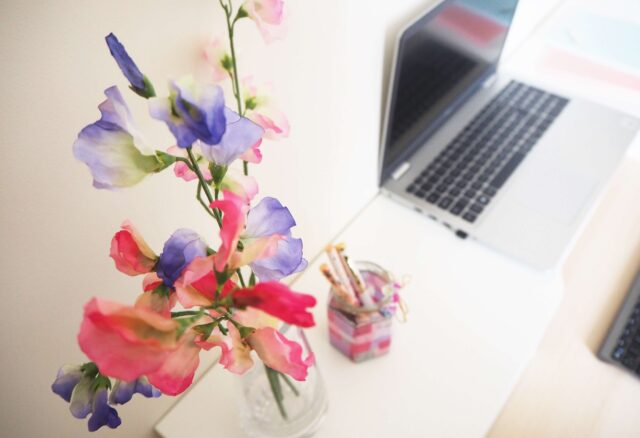 Sweet peas in a vase on a desk next to pen pot and laptop