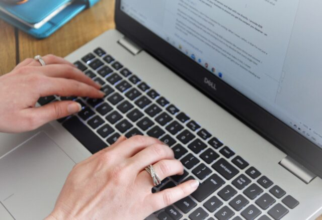 Freelance copywriter female typing on laptop